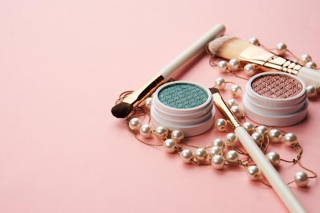 Oogschaduwaccessoires kralen make-up kwasten collectie professionele cosmetica op roze ruimte.