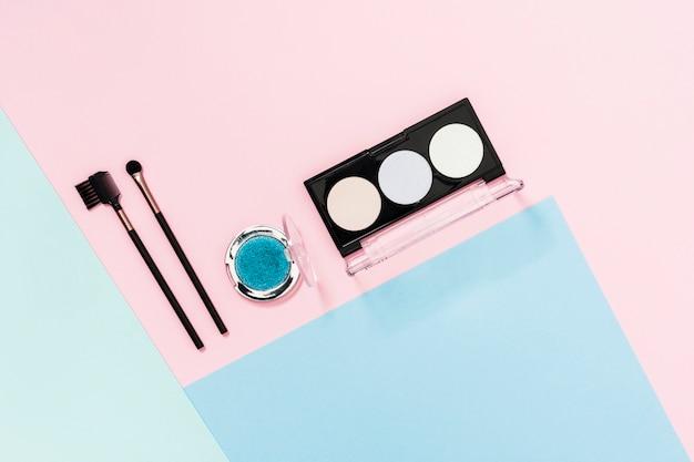 Oogschaduwpalet met make-upborstel op gekleurde achtergrond
