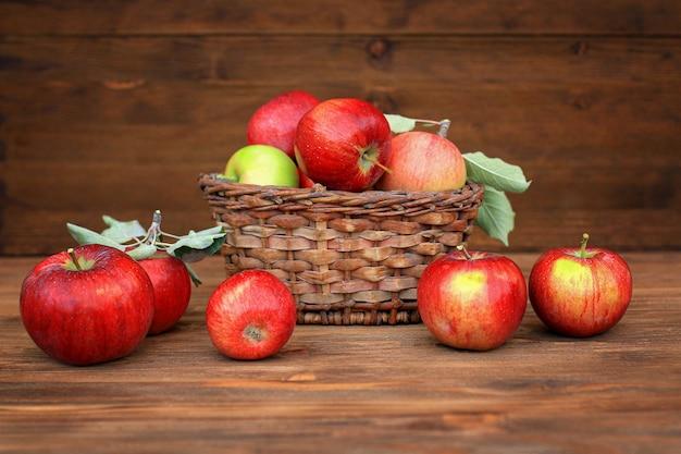 Oogst appels. rode appels in een rieten mand op een oude houten tafel