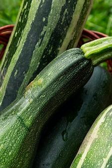 Oogst een verscheidenheid aan courgettes in een rieten mand. vitaminen en gezonde voeding. detailopname. verticaal.