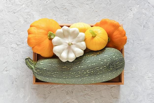 Oogst gekleurde verschillende groenten kalebassen pompoen, courgette, pompoen in een houten doos