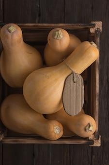 Oogst pompoenen op een houten tafel in een doos, bovenaanzicht
