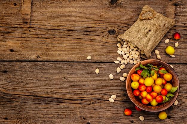 Oogst rijpe kersenpruim. geassorteerde hele vruchten en en zaden op zak. oude houten planken achtergrond, bovenaanzicht