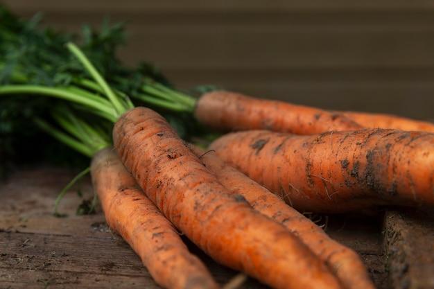 Oogst verse jonge wortelen met topjes. gezonde voeding en vitamines. detailopname. verticaal.