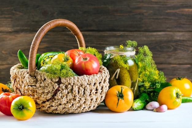 Oogstende groenten, groenten in het zuur in een kruik, verse tomaten in een mand, houten achtergrond