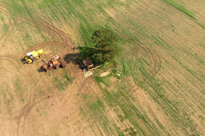 Oogstmachines staan op een breed veld van bovenaf tussen eenzame groene boom en grondweg