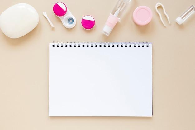 Oogzorgtoebehoren op beige achtergrond met notitieboekjemodel