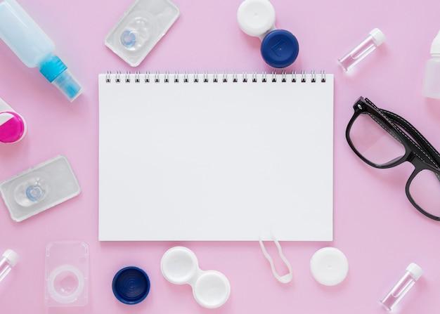 Oogzorgtoebehoren op roze achtergrond met notitieboekjemodel