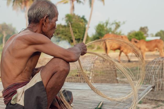 Oom aziatische oude man met rieten hulpmiddelen.