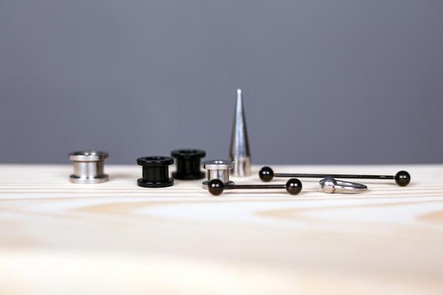Oor piercing set. piercing accessoires op grijze achtergrond close-up.