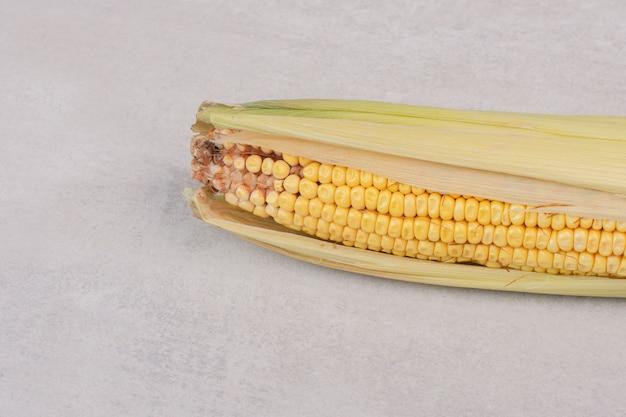 Oor van vers maïs op wit.