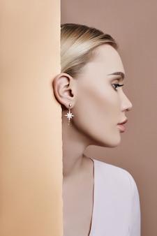 Oorbellen en sieraden in het oor van een blonde vrouw tegen de muur gedrukt