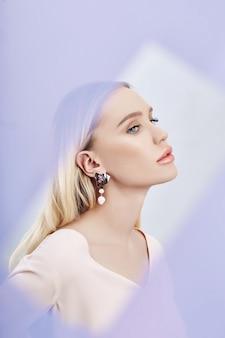 Oorbellen en sieraden in het oor van een sexy blonde vrouw door een transparant gekleurde stof