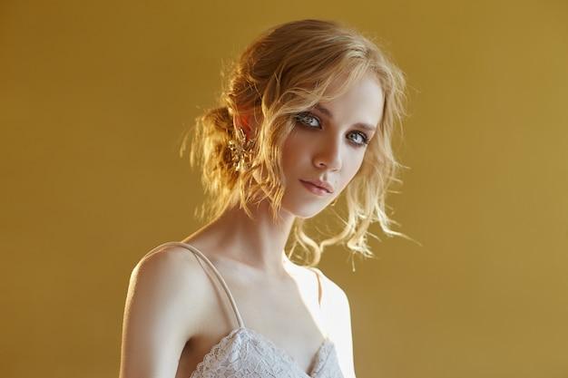 Oorbellen en sieraden in het oor van een sexy blonde vrouw gedrukt. perfect blond meisje, prachtige mysterieuze look. reclame-sieraden, mooie oorbellen in het meisjesoor