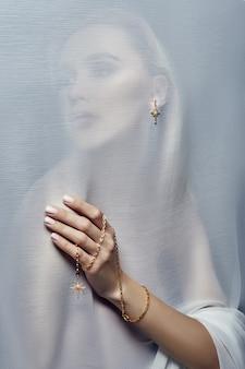 Oorbellen en sieraden in het oor van een sexy vrouw gestoken door een transparante stof. perfect blond meisje, prachtige mysterieuze look
