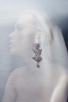 Oorbellen en sieraden in het oor van een sexy vrouw ingebracht door een transparante stof. perfect blond meisje, prachtige mysterieuze look. reclame sieraden, mooie oorbellen in het meisjesoor