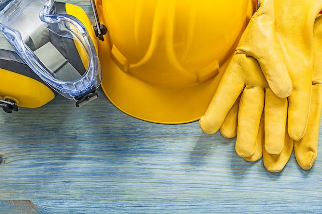 Oorbeschermers veiligheidsbril handschoenen bouwvakker op houten plank bouwconcept