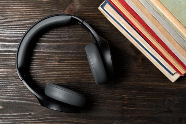 Oordopjes met boeken op houten achtergrond. leren met audioboeken concept. bovenaanzicht