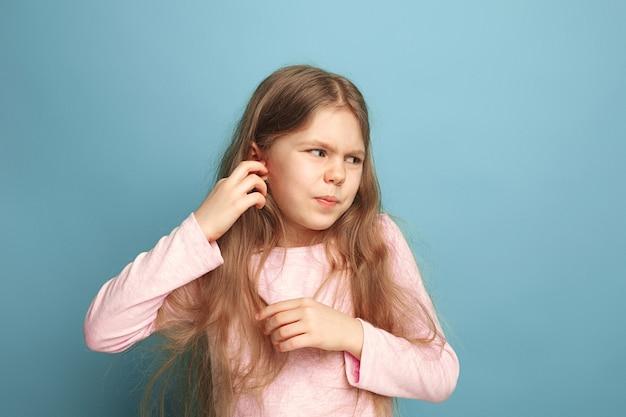 Oorpijn. verdrietig tienermeisje met hoofdpijn of pijn op blauw. gezichtsuitdrukkingen en mensen emoties concept