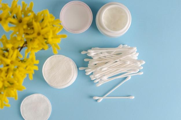 Oorstokken en wattenschijfjes op pastelblauw, make-upverwijdering en huidverzorgingsconcept