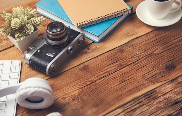 Oortelefoon met toetsenbord en kladblok met camera op tafel
