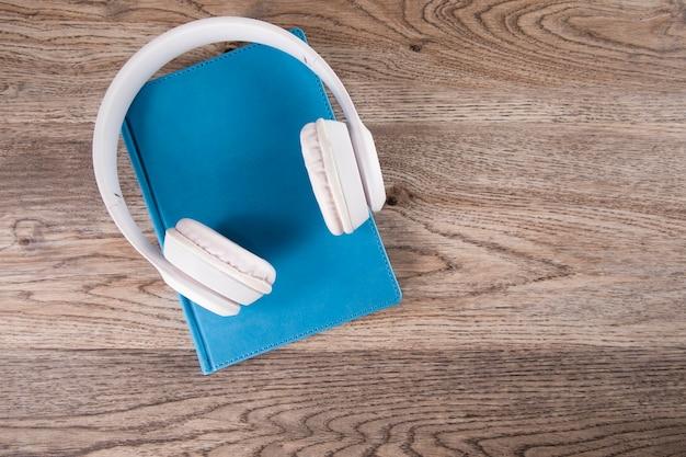 Oortelefoon op boek op houten tafel