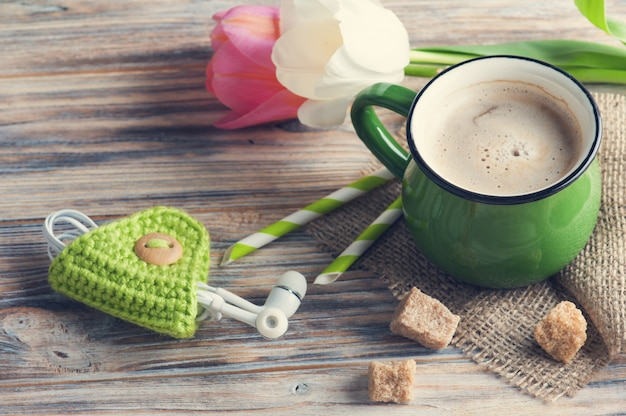 Oortelefoons en mok koffie met tulpen