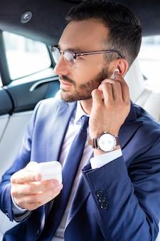 Oortelefoons gebruiken. bebaarde knappe jonge zakenman die oortelefoons gebruikt terwijl hij in de auto zit