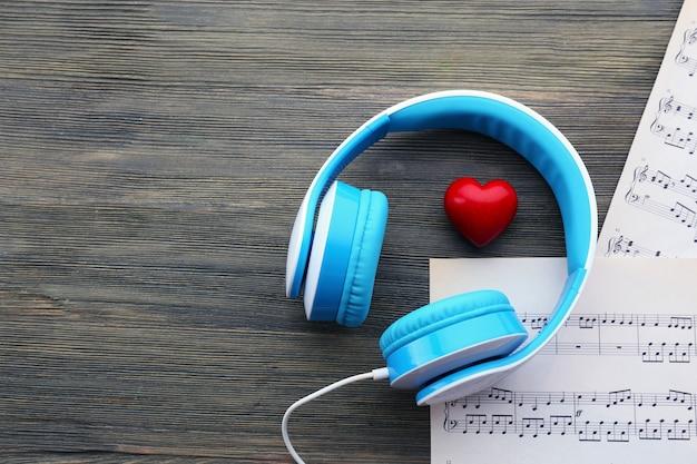 Oortelefoons met rood hart en muziek notities op houten tafel close-up