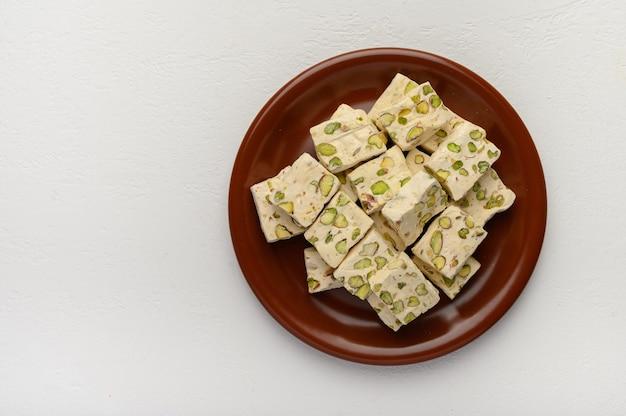 Oost-arabische nougat-zoetheid met pistachenoten op een bruine keramische plaat op een lichte achtergrond.