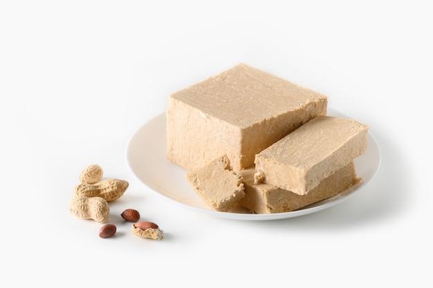 Oost-zoete halva van de dessertpinda in plaat die op witte achtergrond wordt geïsoleerd.