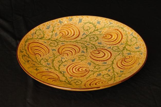 Oosterse antieke ceramische plaat op een zwarte close-up als achtergrond