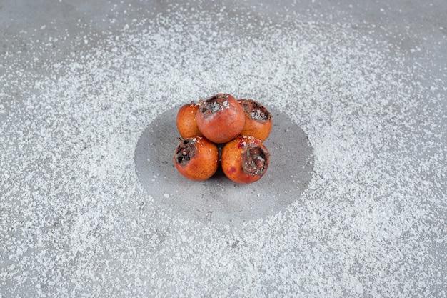 Oosterse dadelpruimen met kokospoeder verspreid over marmeren oppervlak