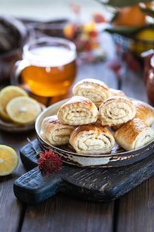 Oosterse dessertgata met een kop thee en mandarijnen op een houten lijst