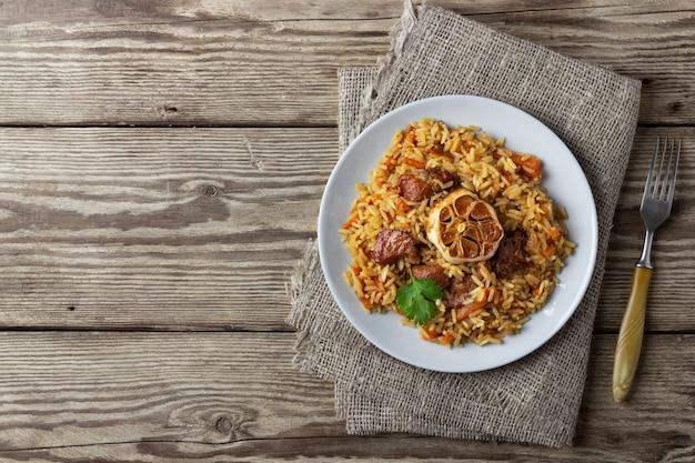 Oosterse keuken. oezbeekse pilaf of plov van rijst en vlees. houten rustieke achtergrond. bovenaanzicht met kopieerruimte.