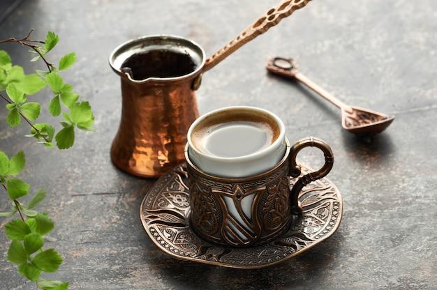 Oosterse koffie gekookt in traditionele turkse koperen koffiepot gegoten in een kopje