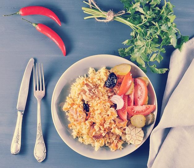 Oosterse schotel plov met gedroogde pruimen, salade met uien en augurken, peterselie