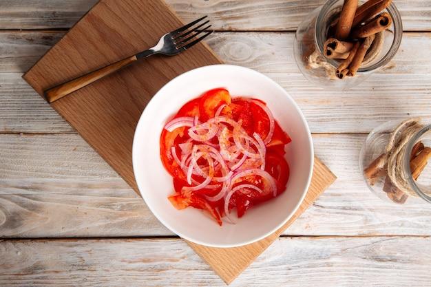 Oosterse tomatensalade achichuk met peper en ui in een witte kom op het houten bord