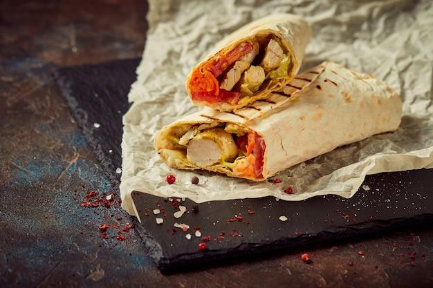 Oosterse traditionele shoarma met kip en groenten, döner kebab met sauzen op leisteen. fast food. oosters eten.