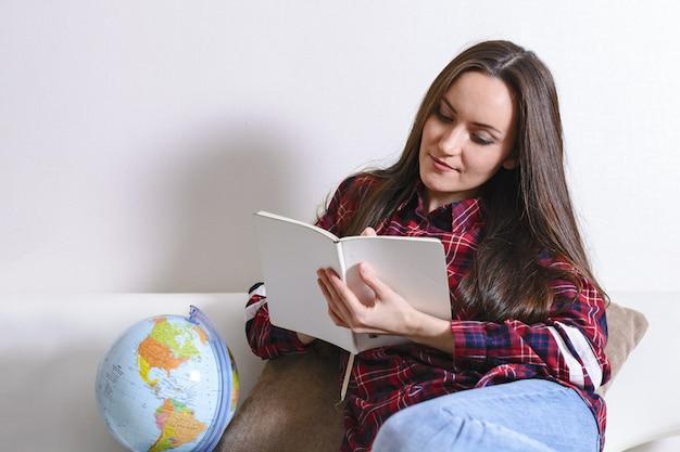 Op avontuur gaan. mooie vrouw die droomt van reizen over de hele wereld, notities maken in een dagboek met reislanden. gelukkig schattige brunette voorbereiden op de reis