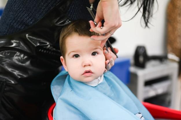 Op bezoek bij een kind bij de kapper. het eerste kapsel van het kind bij de kapper. baby kapsel peuter.