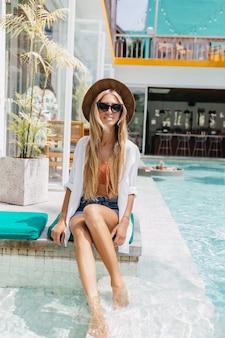 Op blote voeten blonde dame ontspannen in het zwembad in zonnige dag. portret van aangename blonde vrouw in hoed zittend in water.