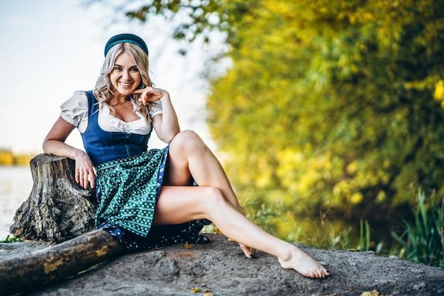 Op blote voeten gelukkig vrij blond meisje in dirndl, traditionele bierfestival jurk, buiten zitten met blured kleurrijke bomen achter