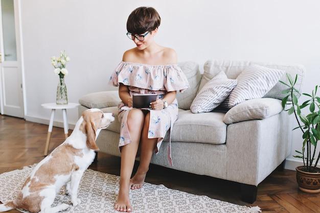 Op blote voeten glimlachend meisje met witte manicure die met liefde hond na het werk met tablet bekijkt