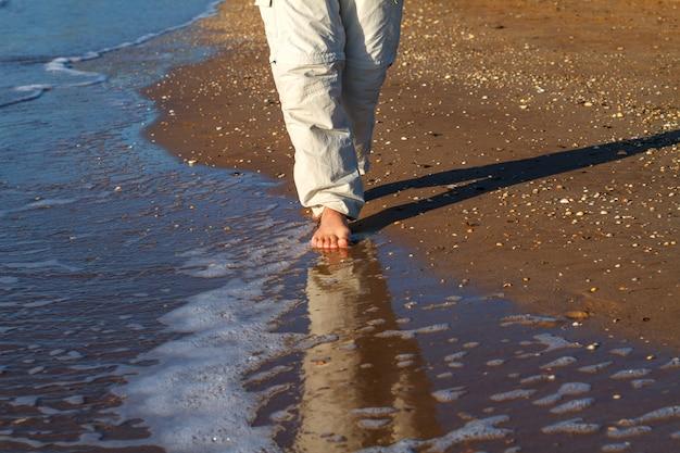 Op blote voeten man lopen op de golven van de branding