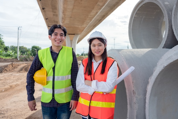 Op de achtergrond, betonnen bekistingsframes van wolkenkrabbers en een portret van een zelfverzekerde vrouwelijke bouwvakker op een bouwplaats.