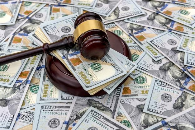 Op de achtergrond van dollars staan dollars, en daarop ligt de hamer van de rechter
