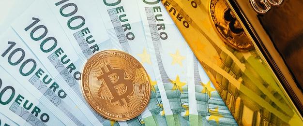 Op de achtergrond van eurobiljetten, een grote glanzende goudstaaf en een bitcoin-munt