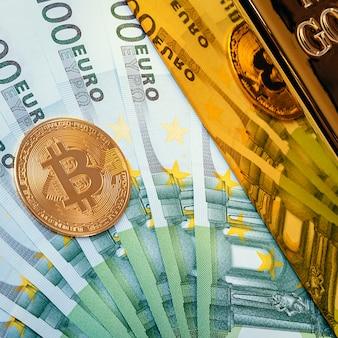 Op de achtergrond van eurobiljetten, een grote glanzende goudstaaf en een bitcoin-munt.