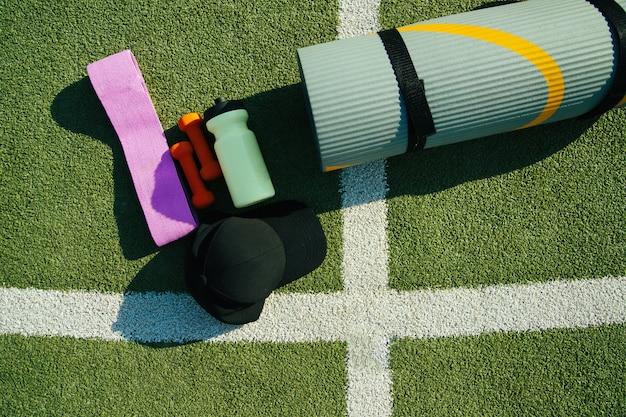 Op de achtergrond van kunstgras is er een mat, een fles, een fitness elastische band en een mat. sportuitrusting. het concept van een gezonde levensstijl, sport en dieet. een zonnige dag.